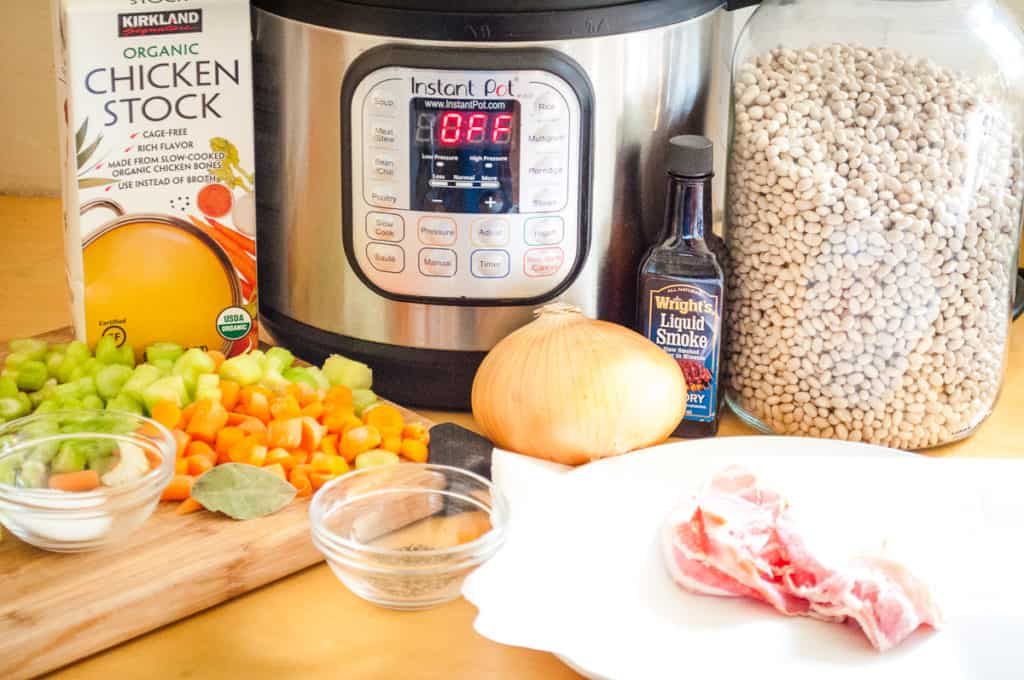 all the ingredients for a homemade bean soup recipe made quickly in the instant pot-celery, carrots, bacon, seasonings, dried beans, broth and of course the instant pot.