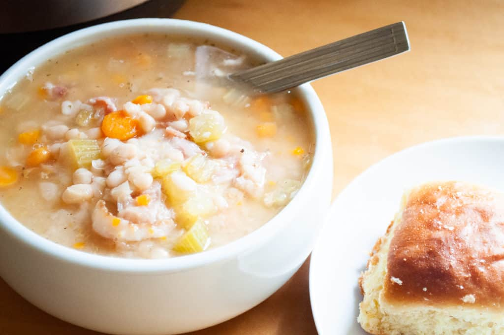 A tighter shot of the fresh homemade bean soup recipe. This picture has a bowl of soup, with a spoon tucked in it, and small part of the bread roll on a plate is showing.