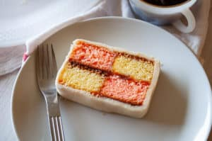 A slice of Battenberg cake showing it's pink and yellow checker board pattern.