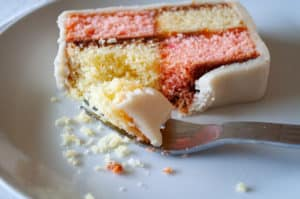 A Battenberg Cake Slice with a piece of cake on a fork.