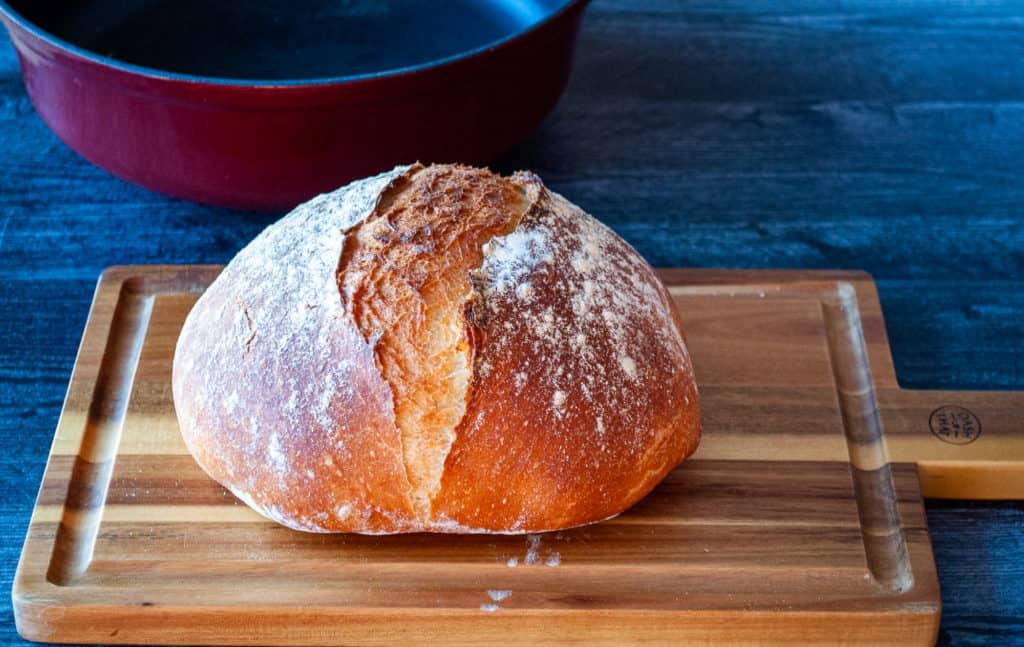 A fresh loaf of bread on a cutting board.