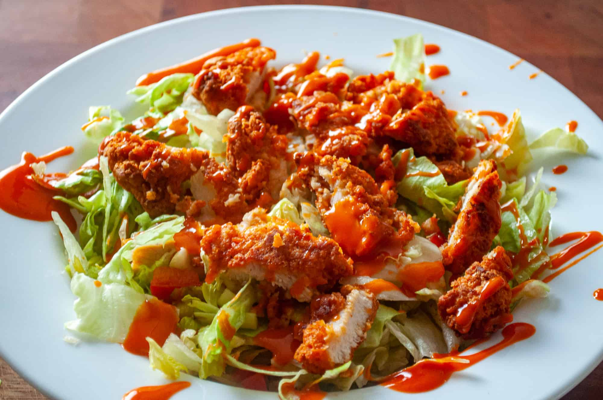 Buffalo chicken on a salad.