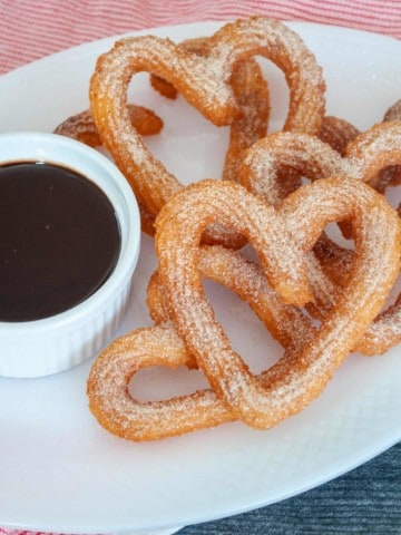 Plate with chocolate dipping sauce and heart shaped churros.