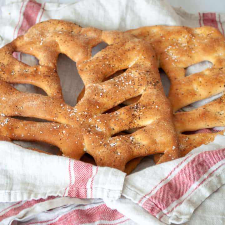 Two loaves of fougasse bread in a towel.