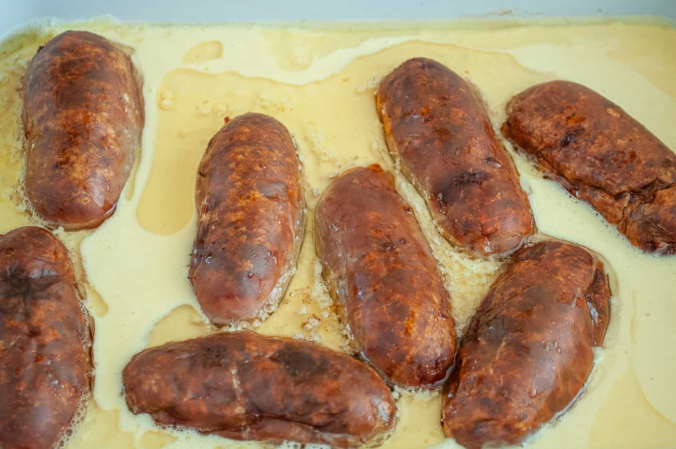 Sausages surrounded by yorkshire pudding batter.